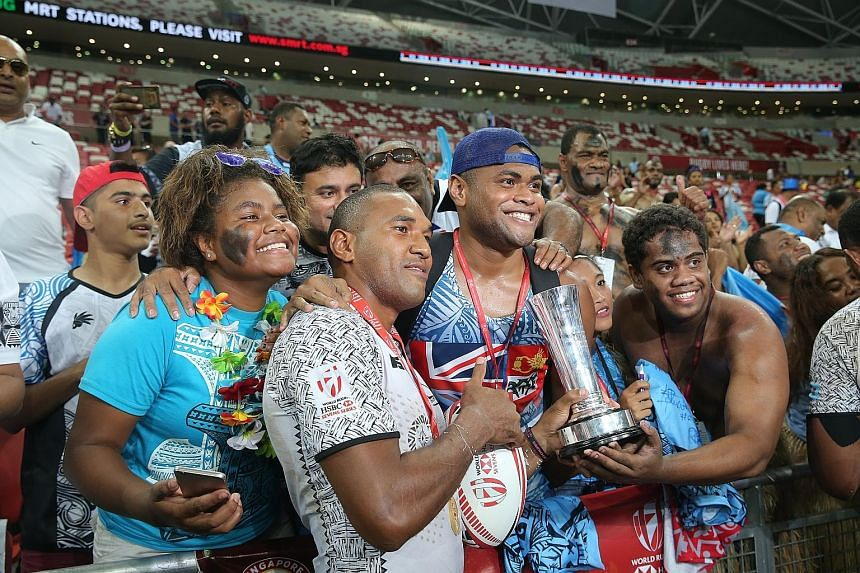 Top: Fiji's Waisea Nacuqu, the Man of the Match, sprinting towards a try. Fiji beat Australia with a late converted try - the third different team to earn the title in Singapore since the series returned in 2016. Above: Fiji players greeting their de