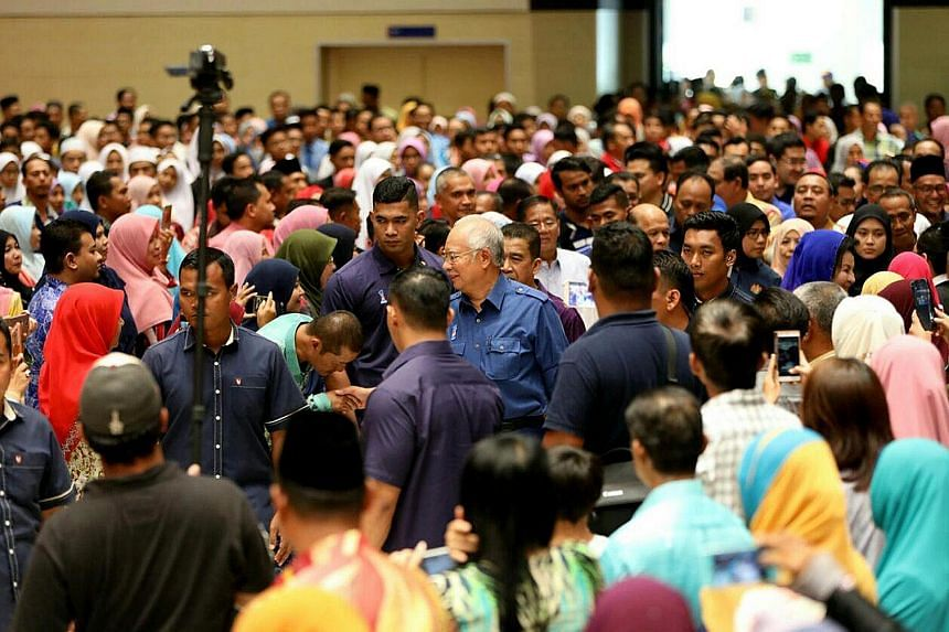 Above: Former premier Mahathir Mohamad posing for photos with people yesterday at Pasar Kuah in Langkawi, Kedah. He is contesting the seat for the first time but is no stranger to residents, with many crediting him with transforming the island into a