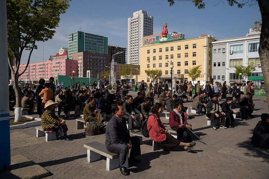 People watching a television broadcast of a meeting of the ruling Workers' Party's central committee in Pyongyang on April 21. The two Koreas have had different time zones since 2015 when the North changed its standard time to 30 minutes behind the S