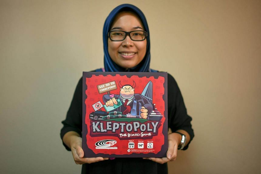 An employee of the Centre to Combat Corruption and Cronyism (C4) posing with the Kleptopoly board game in Petaling Jaya, Kuala Lumpur.