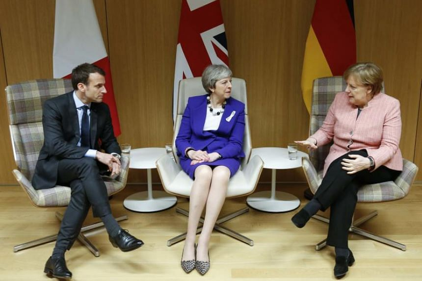 Britain's Prime Minister Theresa May is flanked by French President Emmanuel Macron and German Chancellor Angela Merkel before their trilateral meeting at the European Union leaders summit in Brussels, Belgium, on March 22, 2018.