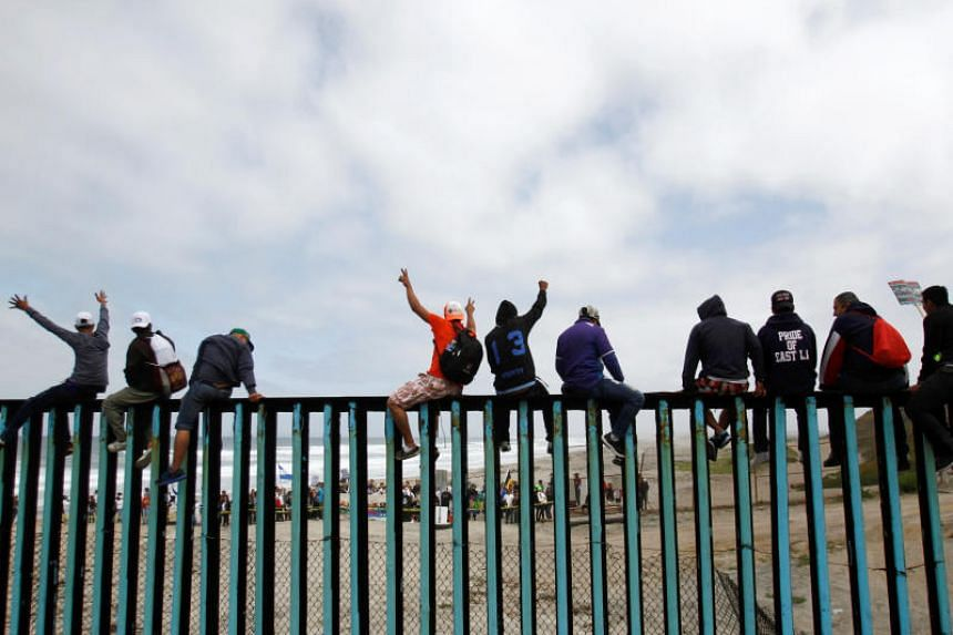 Members of a caravan of migrants from Central America wave to supporters in the United States, while sitting on the border fence between Mexico and the US as part of a demonstration, prior to preparations for an asylum request in the US, in Tijuana,