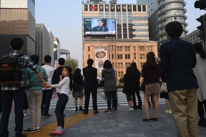 Pedestrians watch live footage of a joint press conference between South Korean President Moon Jae In and North Korean leader Kim Jong Un during the inter-Korea summit, in downtown Seoul on April 27, 2018.