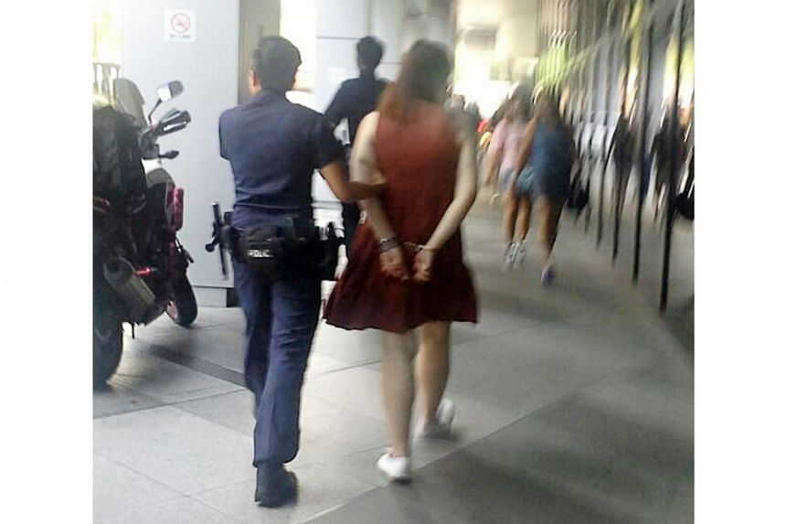The female suspect being led away by police after allegedly stealing make-up products from a cosmetics store in Ion Orchard shopping mall.