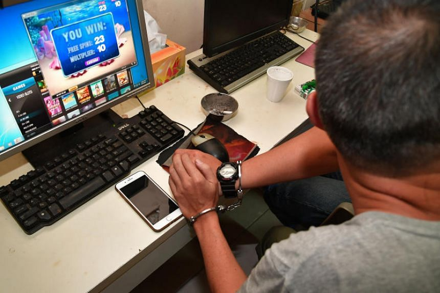 A man placed in handcuffs following a raid by police on an illegal gambling den in Petain Road on March 23, 2018.