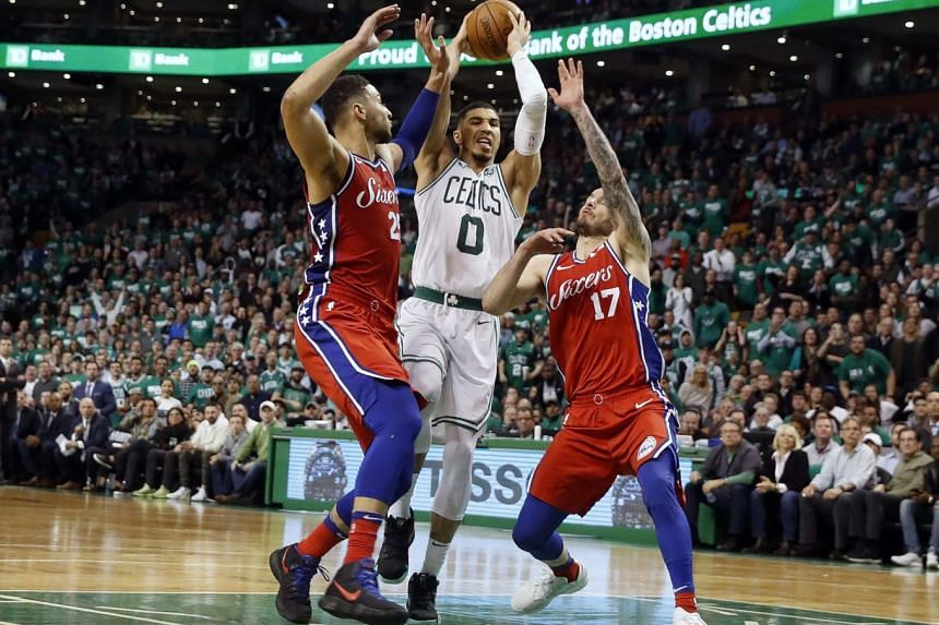 Boston Celtics forward Jayson Tatum driving between Philadelphia 76ers guard Ben Simmons (left) and guard J.J. Redick during the second half of Boston's 117-101 win in game one of the second round of the NBA Playoffs at TD Garden.