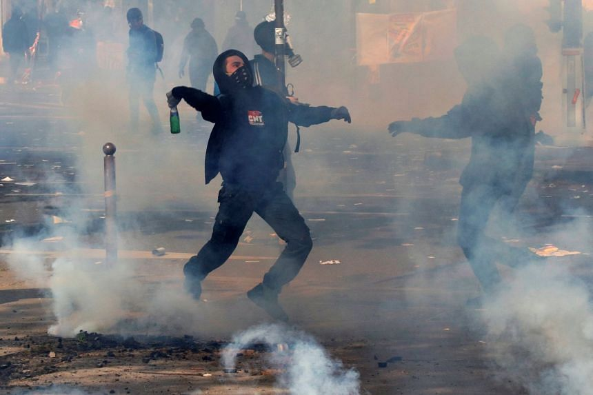Tear gas floats in the air as a masked protester throws a bottle during clashes with French CRS riot police.