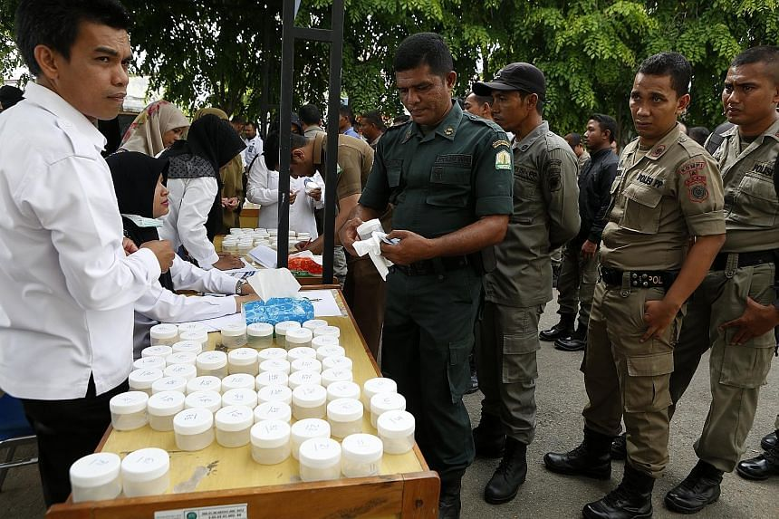 Hundreds of officers from Aceh's syariah and municipal police force queueing up to undergo a drug test at the National Narcotics Agency in Banda Aceh, Indonesia, yesterday. Indonesian President Joko Widodo is urging an increase in efforts to fight il