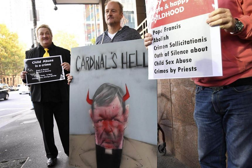 Protesters hold up placards as Vatican finance chief Cardinal George Pell arrives in court in Melbourne, on May 1, 2018.