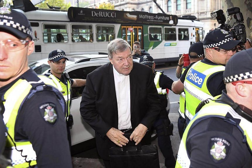 Vatican finance chief Cardinal George Pell (centre) arrives in court in Melbourne, on May 1, 2018.