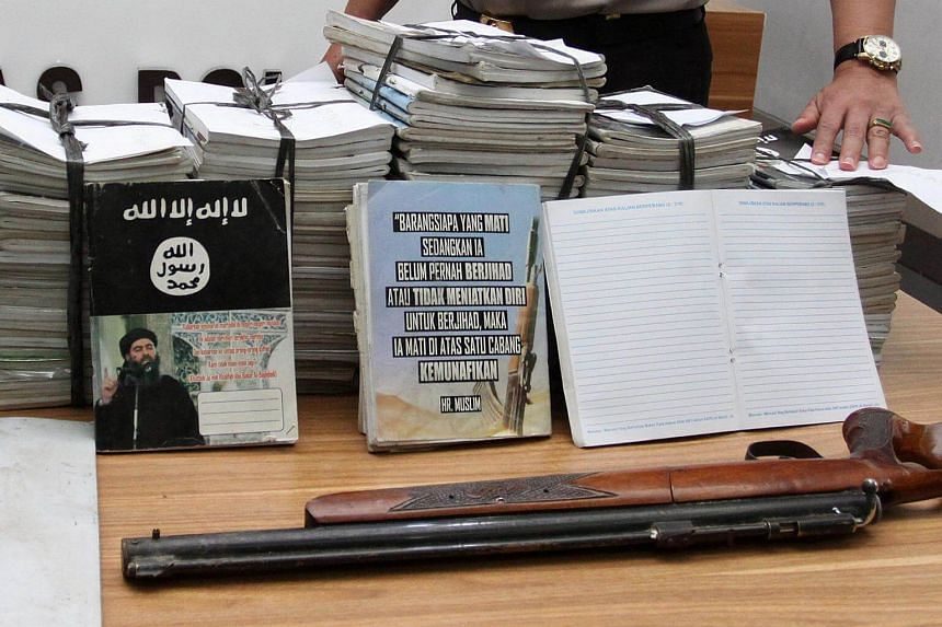 Indonesian police show scores of notebooks inscribed with ISIS propaganda seized during a raid on the home of suspected militant during a press conference at police headquarters in Jakarta, Indonesia, on June 30, 2017.