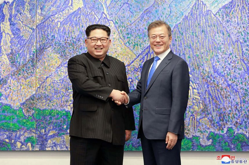 North Korea's leader Kim Jong Un shaking hands with South Korea's President Moon Jae In during the Inter-Korean summit in the Peace House building on the southern side of the truce village of Panmunjom.