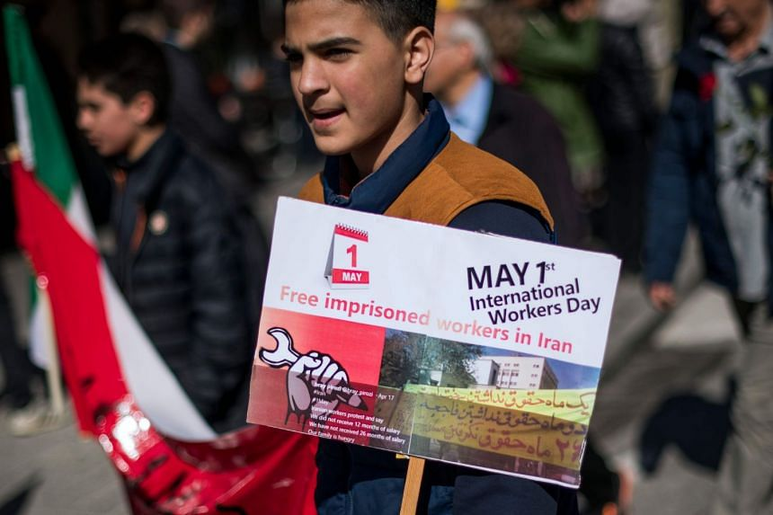 """A protester holds a sign reading """"Free imprisoned workers in Iran"""" as he takes part in a May Day rally in Sweden."""