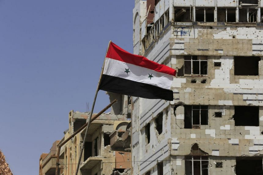 A Syrian government flag flying in the Eastern Ghouta town of Douma on the outskirts of the capital Damascus.