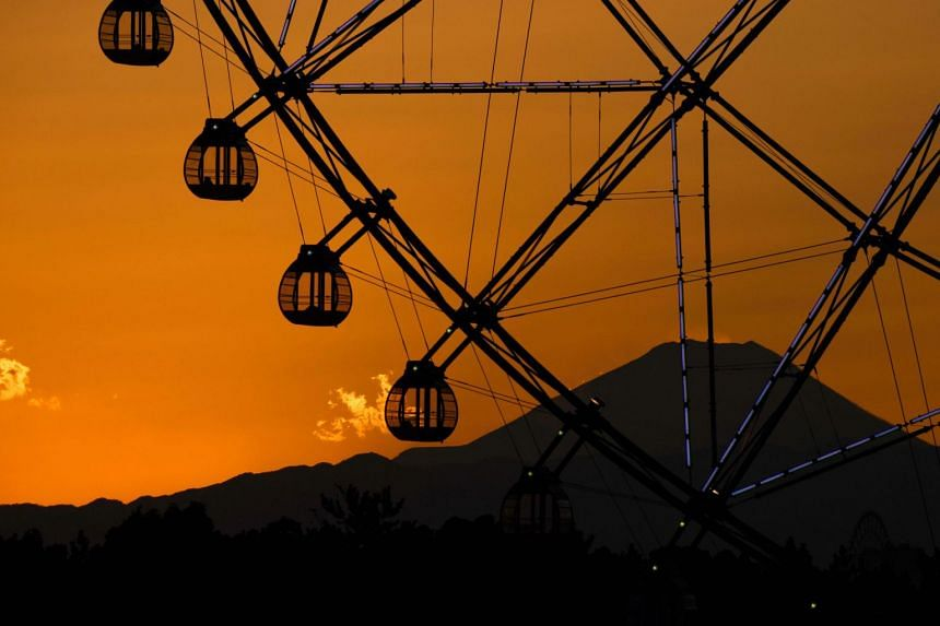 Mount Fuji is seen in the background over a ferris wheel during sunset at Kasai Rinkai Park in Tokyo.