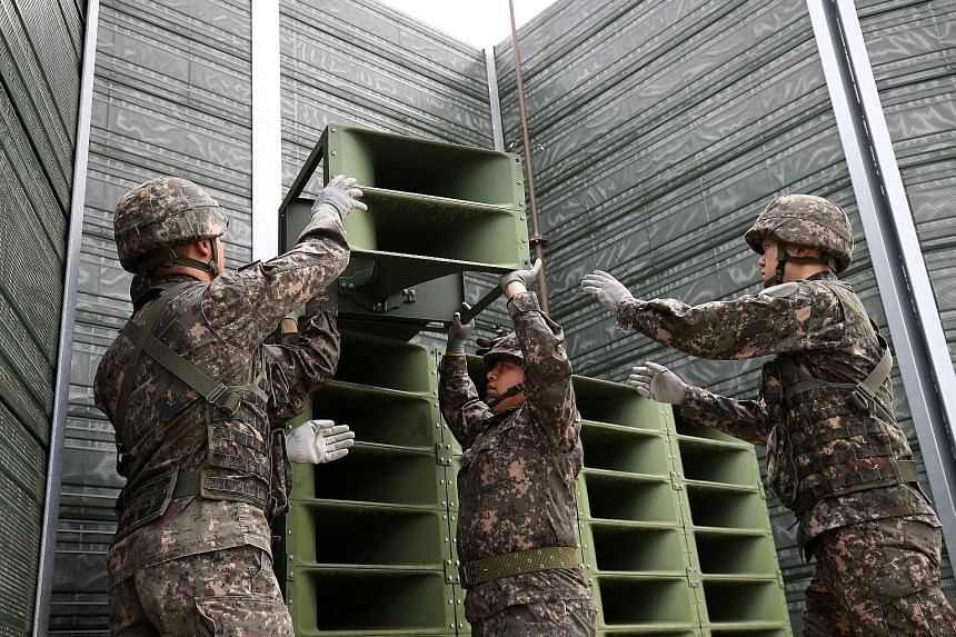 South Korean soldiers taking down a propaganda loudspeaker on the border with North Korea yesterday.