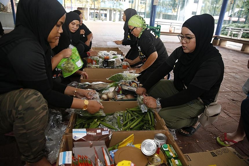 Sincere Hope's founders, Ms Renemarlina Osman (far left) and Madam Normah Ahmid. The group started as an unofficial initiative but came together officially last September. Volunteers unpacking and organising the food to be distributed to beneficiarie