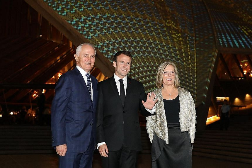 France's President Emmanuel Macron flanked by Australia's Prime Minister Malcolm Turnbull and his wife Lucy outside the Sydney Opera House yesterday.