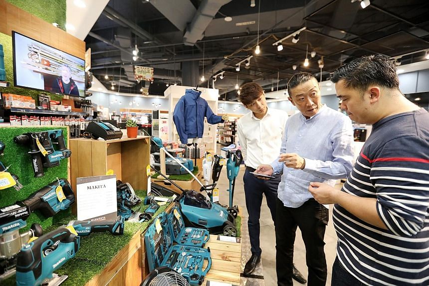 """Cabby David Chan no longer treats Grab as """"the enemy"""", after trying it out and finding that he had more bookings and was earning more. Home-Fix managing director Low Cheong Kee (centre) has transformed his business model to offer more services, such"""