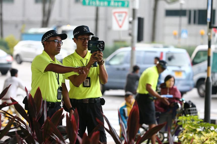 Active Mobility Enforcement Officers (AMEOs) use a speed gun to spot speeding PMD users.