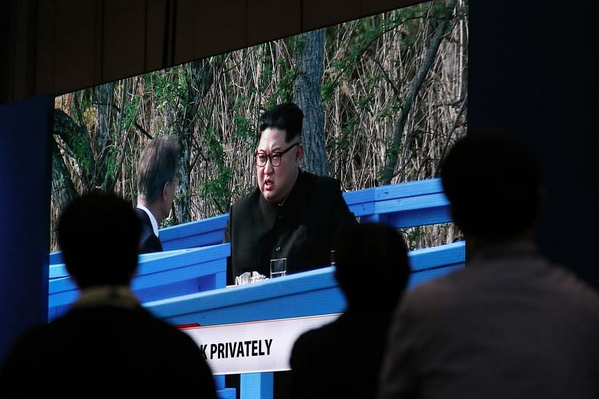 Members of the media watching a broadcast of South Korea's president Moon Jae In (left) and North Korea's leader Kim Jong Un talking privately outside the truce village of Panmunjom.