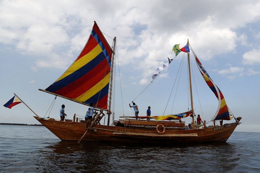 """A Filipino crew sails off aboard the wooden boat """"Sultan Sin Sulu"""" from Manila Bay, Philippines, on April 28, 2018."""