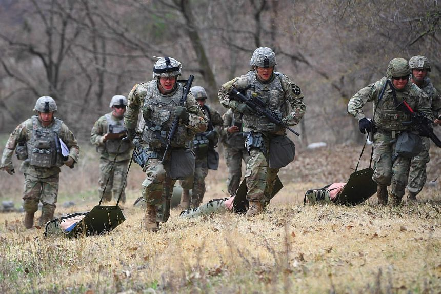 US soldiers running with a dummy during a competition at Camp Casey in Dongducheon, north of Seoul, Korea, on April 10, 2018.