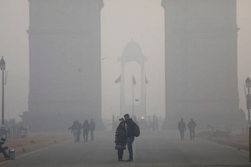 People taking a selfie in front of the India Gate war memorial on a smoggy winter morning in New Delhi, India, on Dec 26, 2017.