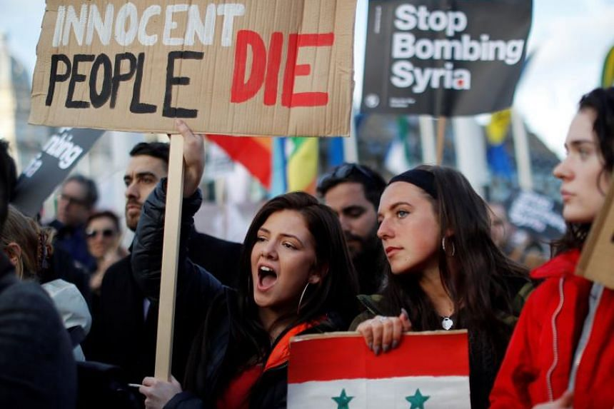Protestors carry placards as they demonstrate against the UK's military involvement in Syria, outside the Houses of Parliament in central London on April 16, 2018.