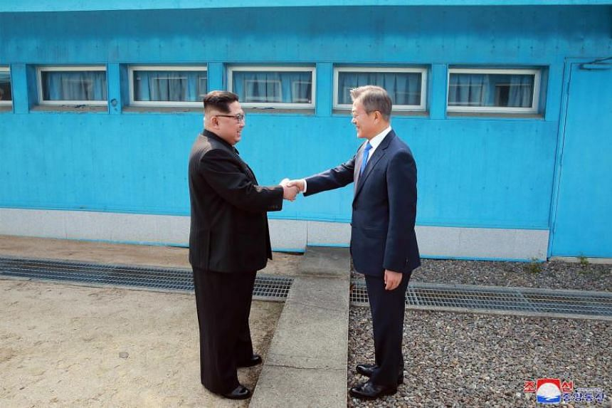 North Korea's leader Kim Jong Un (left) shaking hands with South Korea's President Moon Jae In at the Military Demarcation Line that divides their countries ahead of their summit at the truce village of Panmunjom on April 27, 2018.