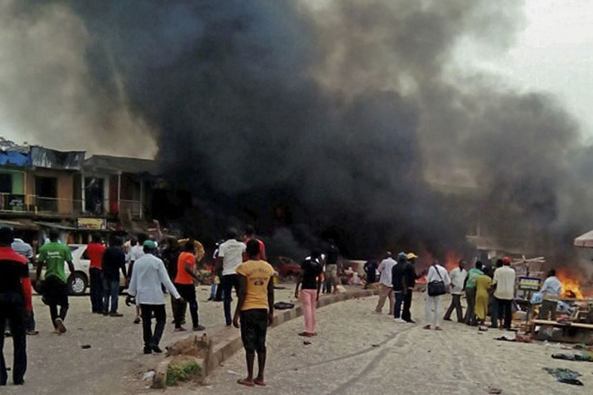 Nigerians look on at the scene of a bomb blast at the Gwonjo market and mosque in Mubi.
