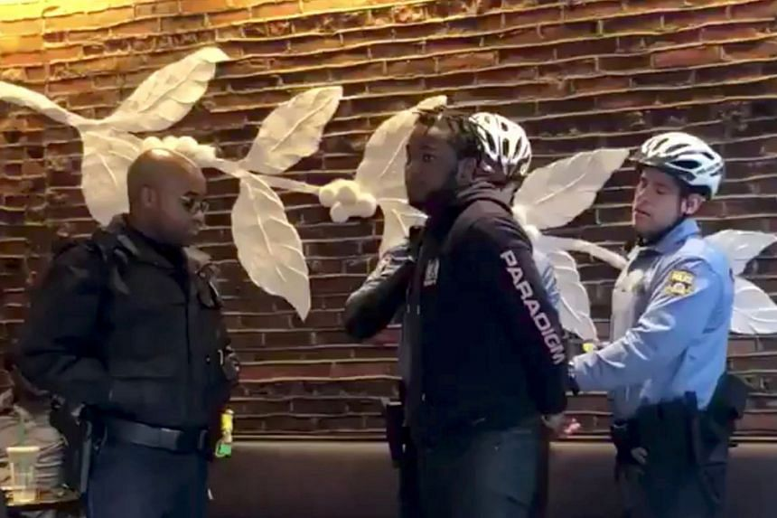 Police detain a man at a Starbucks in Philadelphia, in a picture grab obtained from a social media video.
