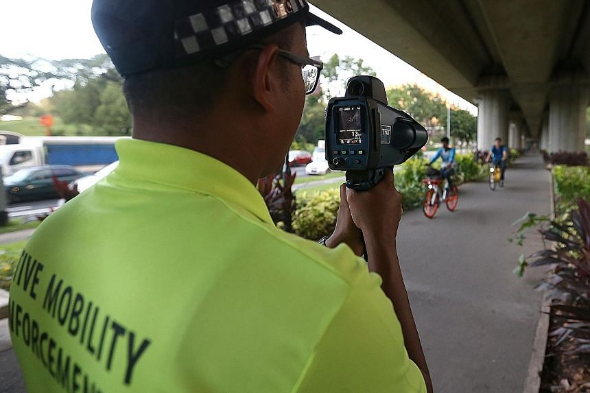 An active mobility enforcement officerusing a speed gun to spot speeding cyclists and PMD users during the enforcement blitz yesterday.