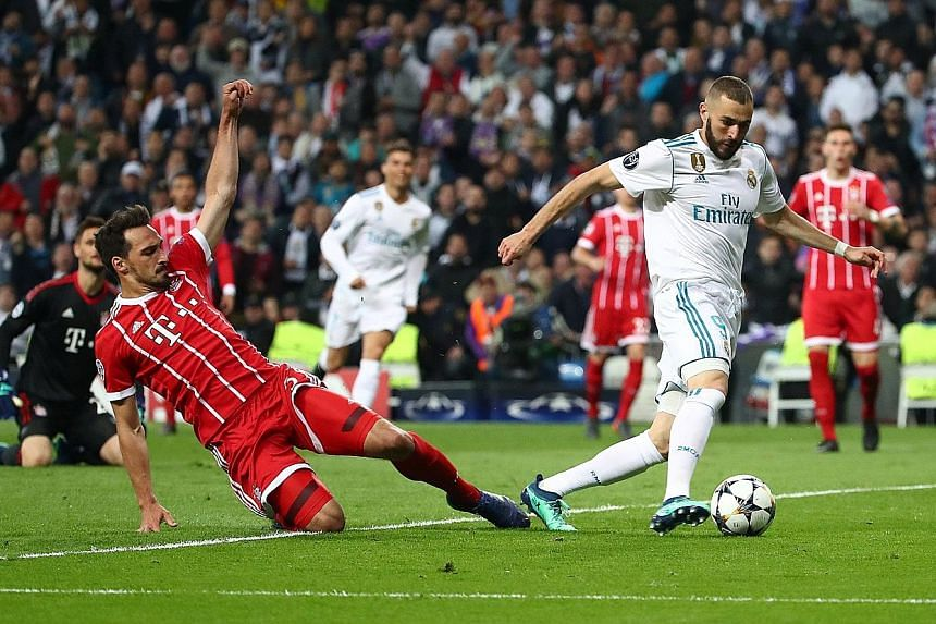 Real Madrid's French forward Karim Benzema celebrating with his team-mates after scoring a second goal (above), following a howler by Bayern Munich goalkeeper Sven Ulreich during the Champions League semi-final return leg at the Santiago Bernabeu on