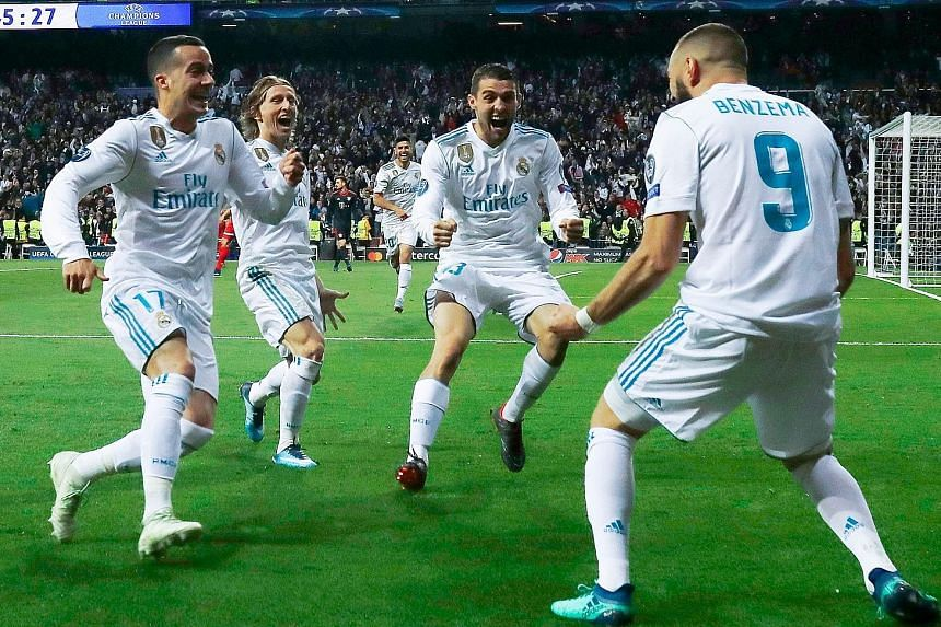 Real Madrid's French forward Karim Benzema (right) celebrating with his team-mates after scoring a second goal, following a howler by Bayern Munich goalkeeper Sven Ulreich during the Champions League semi-final return leg at the Santiago Bernabeu on