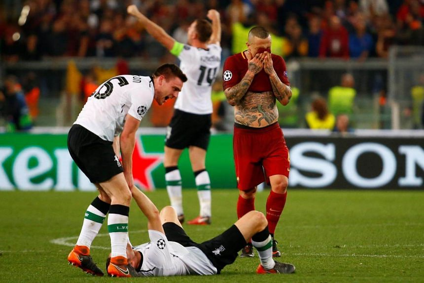 Roma's Radja Nainggolan looking dejected after the match as Liverpool's Andrew Robertson and team mates celebrate.