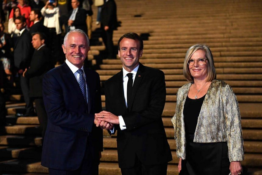 French President Emmanuel Macron (centre) posing for a photo with Australia's Prime Minister Malcolm Turnbull and his wife Lucy Turnbull outside the Sydney Opera House.