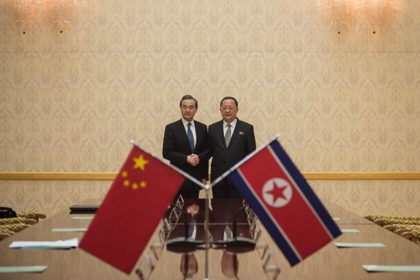 China's Foreign Minister Wang Yi (left) shaking hands with North Korea's Foreign Minister Ri Yong Ho at the Mansudae Assembly Hall in Pyongyang on May 2, 2018.