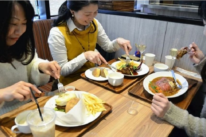 """People eat dishes made with ingredients available for sale at a """"grocerant"""" in the Seijo Ishii Trie Keio Chofu store in Chofu, Tokyo."""