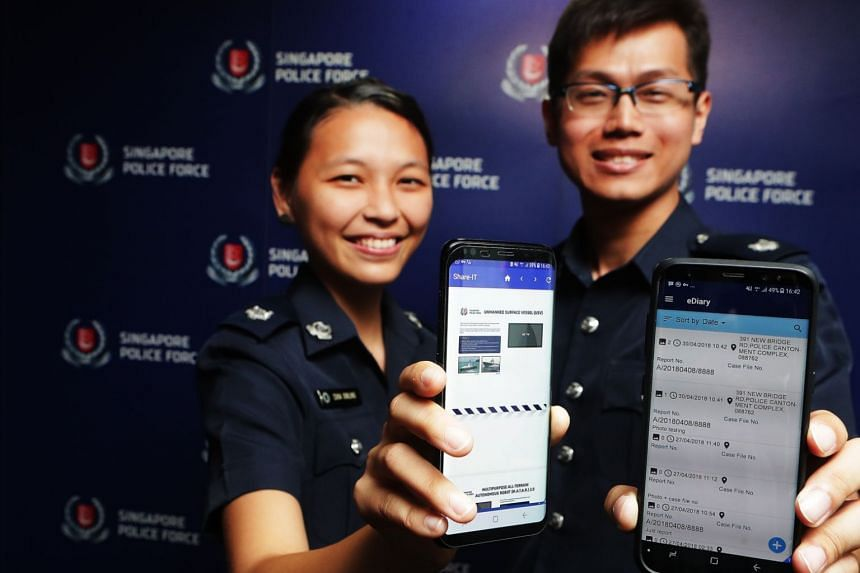 Assistant Superintendents Chia Xinling (left) and Lee Ting Wei holding the police smartphone.