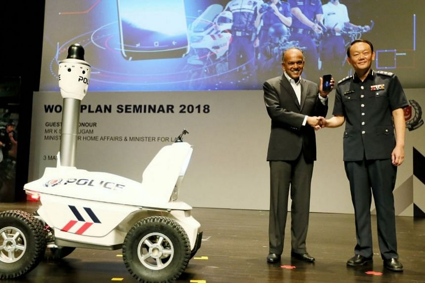 Home Affairs Minister K. Shanmugam holding a police smartphone as he shakes the hand of Commissioner of Police Hoong Wee Teck at the Singapore Police Force's annual workplan seminar.