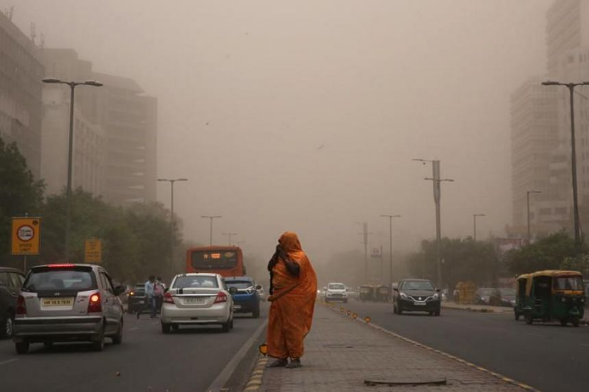 A woman walks with her face covered to avoid a dust storm in New Delhi, India, on May 2, 2018.