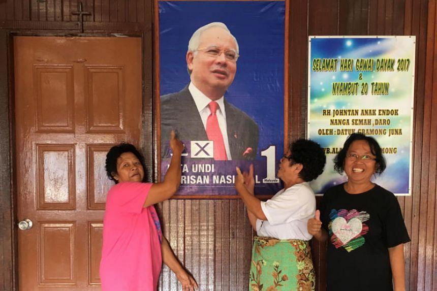 Women posing for photos with a portrait of Malaysia's Prime Minister Najib Razak at Nanga Semah village in Sarawak on April 24, 2018.