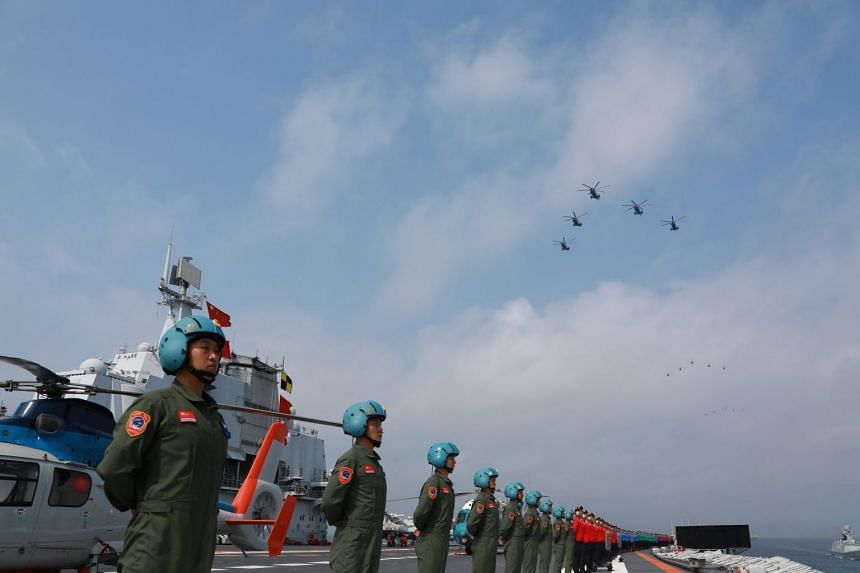 Personnel of the Chinese People's Liberation Army Navy take part in a military display in the South China Sea.