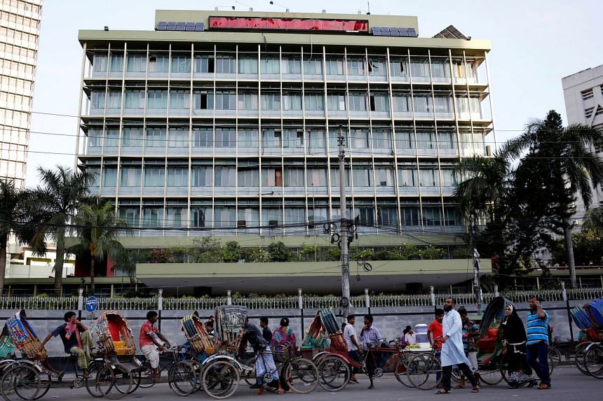 Commuters walk in front of the Bangladesh central bank building in Dhaka, Bangladesh.