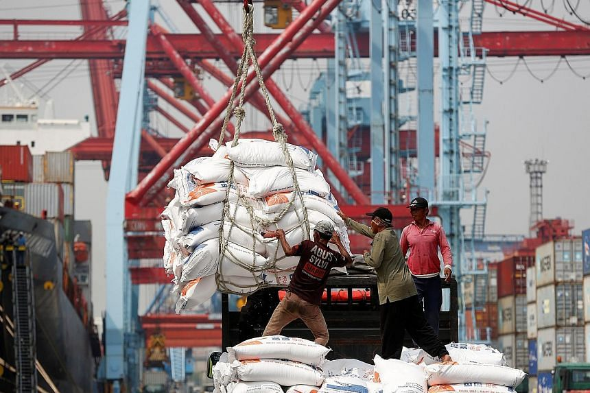 Workers unloading bags of rice from a cargo ship onto a truck at Tanjung Priok Port in Jakarta. The Asean+3 Macroeconomic Research Office said in its report that stronger global growth has helped the region build up buffers against potential external