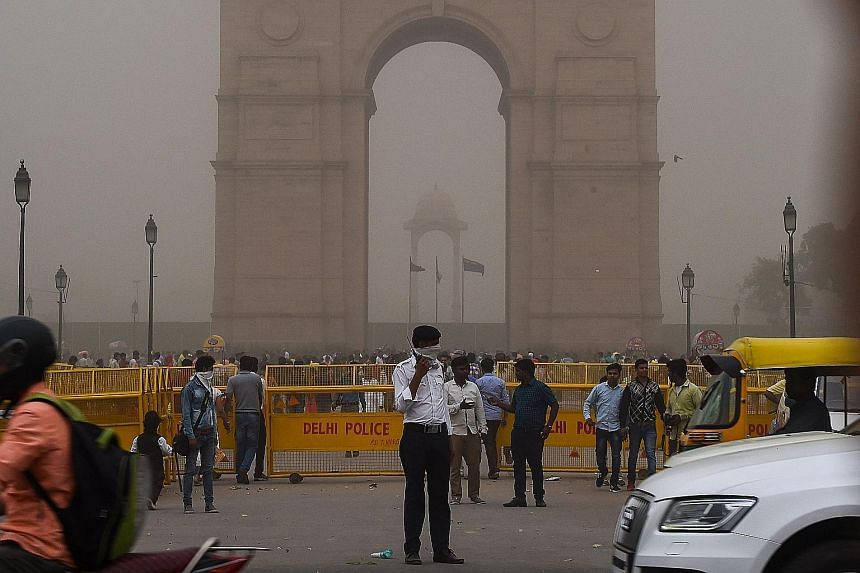 A traffic policeman with half his face covered during a dust storm in New Delhi on Wednesday. Scientist Charan Singh of the India Meteorological Department said winds of 132kmh hit Agra, while in Delhi, there were winds of 59kmh.