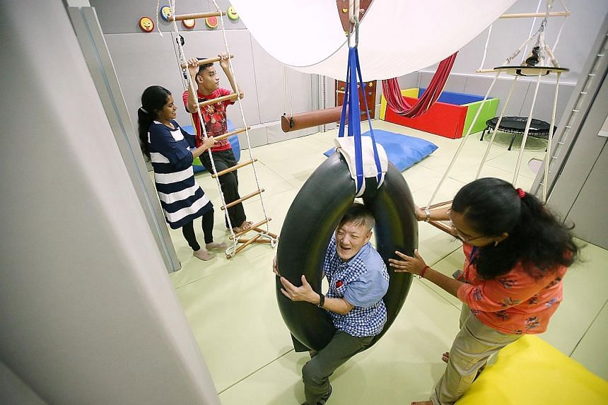 Mr Yap Koon Seng trying out the tyre swing under the watchful eye of therapist Sivasankari Neelothpalam. Far left, Muhammad Nor Hanis Azman climbing the rope ladder with the help of therapist assistant Anthonysamy Mary Kavi Nevadha.