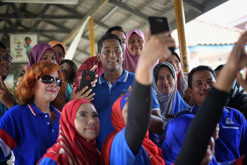 Pakatan Harapan's Tony Pua at a rally in Yong Peng last night. Masks of Dr Mahathir Mohamad, whose photo cannot be used on campaign material, were passed around. Barisan Nasional Youth chief Khairy Jamaludin during a walkabout in Seremban, Negeri Sem