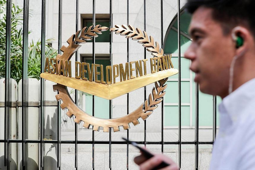 A security personnel walks past the gate of the Asian Development Bank (ADB) headquarters in Mandaluyong City, in Manila, Philippines, on May 3, 2018.